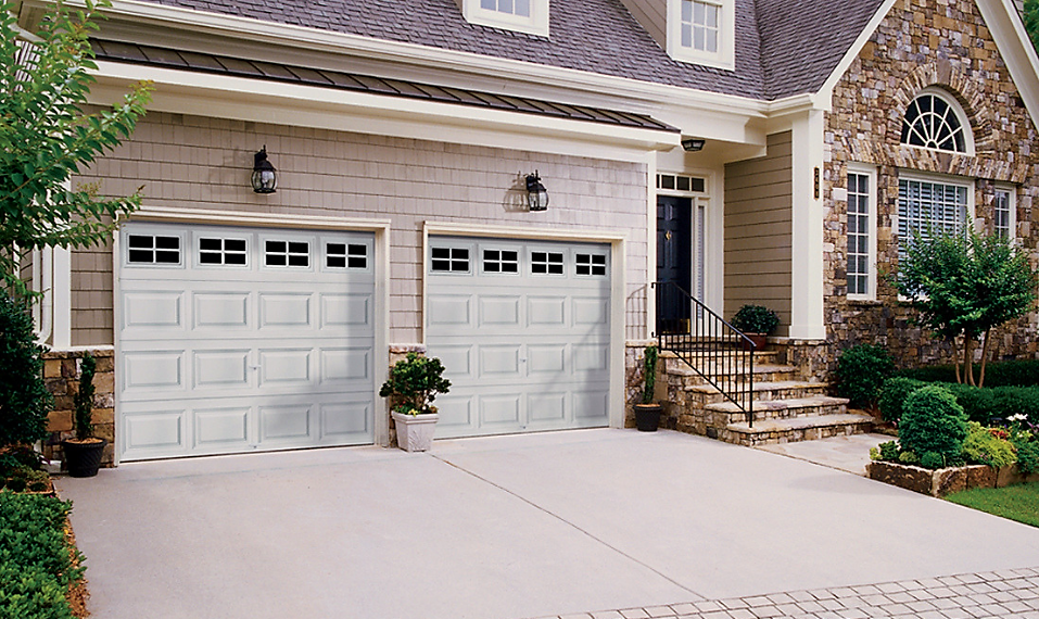 brick house with double white garage doors