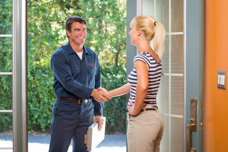 workman greeting woman at the front door